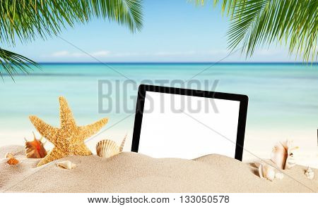 Summer concept with empty tablet display for copyspace. Various kind of shells in sand. Palm leaves on foreground