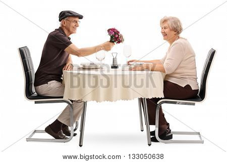 Mature man giving flowers to his wife seated on a date at a dinner table isolated on white background