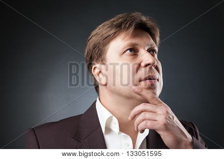 Headshot pf adult businessman looking up and thinking.