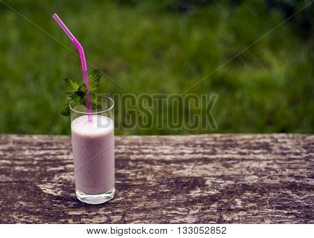 Strawberry milkshake with mint on old rustic wooden background.