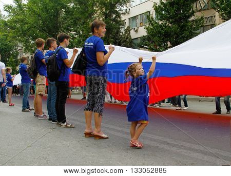 VOLGOGRAD, RUSSIA - JUNE 12, 2015: Little girl together with other activists hold a large Russian flag on the Independence day of Russia in Volgograd