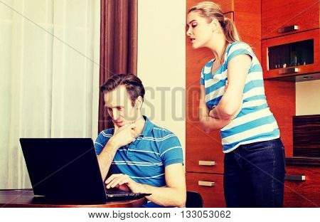 Man watching something on laptop, his wife trying to look what he doing