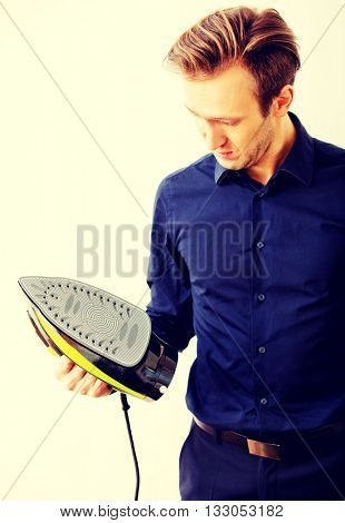Young businessman ironing his jacket