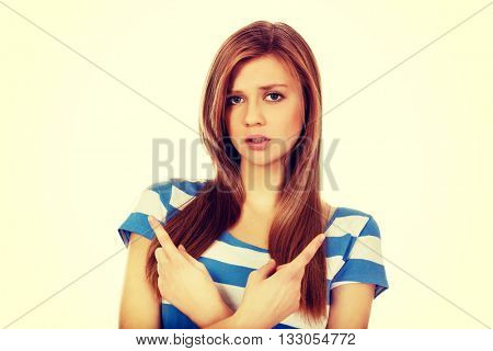 Confused teenage woman pointing in two different directions
