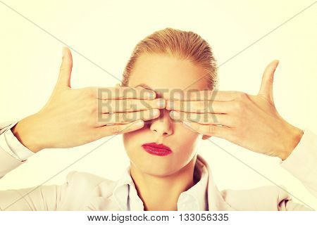 Business woman covering her eyes with her hands. See no evil concept