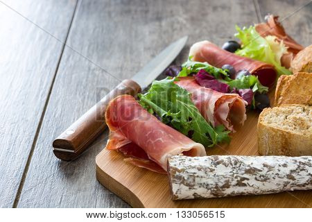 Spanish serrano ham, olives and sausage on a rustic wooden table