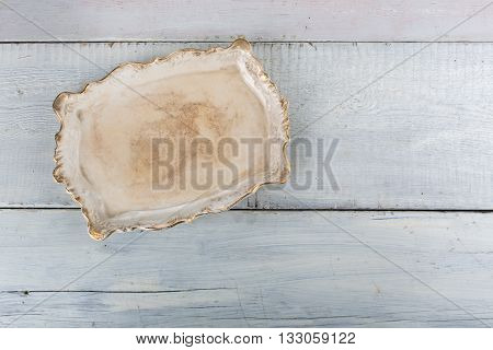 White vintage porcelain tray on white wooden background, top view