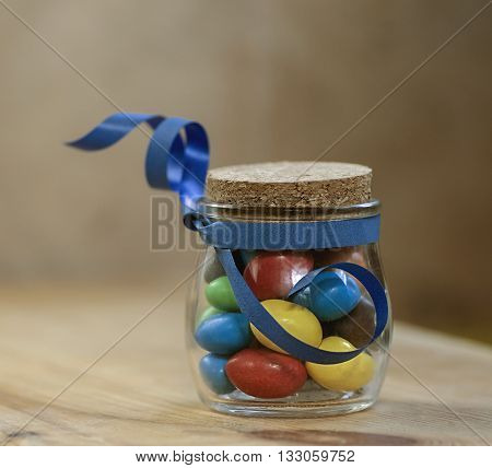 candy jelly beans in a jar with a cork tied with a blue ribbon