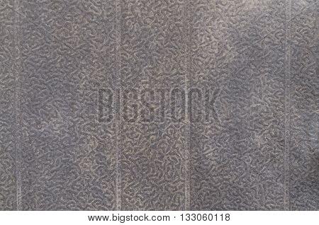 Black metal plate with bumpy surface closeup