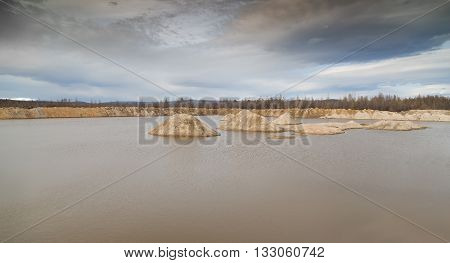 an abandoned sand quarry with mountains of sand filled with water in bad weather