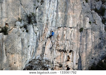 Young Man Climbing a Cliff of Mountain
