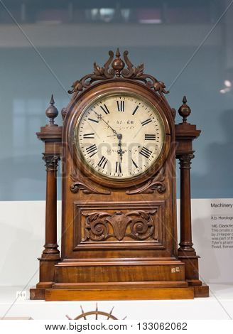 SCIENCE MUSEUM, LONDON - FEBRUARY 08, 2016: Single wooden antique clock with ornate carving decoratation on display inside glass case. London, UK on February 08, 2016.