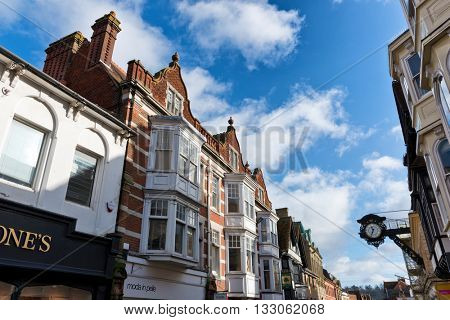 WINCHESTER, UK - FEBRUARY 07: Low angle view looking down a Winchester, England street towards clock on building under blue sky with white clouds. Winchester, UK on February 07, 2016.