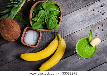 A glass of green smoothies and the ingredients from which it was made. Smoothies with spinach banana coconut water pineapple on gray wooden table.