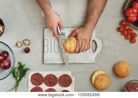 Male cook is preparing burgers on a white table top view