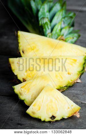 Pineapple chunks on gray wooden background. Fresh pineapple.