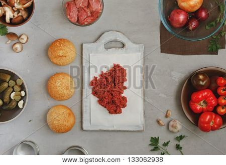 Fresh minced beef on a white kitchen board with buns with sesame seeds and vegetables on a white surface. Ingredients for making burgers top view