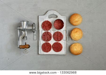 Fresh beef patties for burgers with vintage meat grinder and buns with sesame seeds on a white surface top view. Flat lay