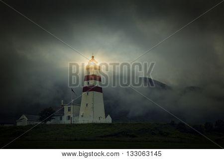 Lighthouse at foggy day, Fishing Village In Godoya Island - Giske, Romsdal county, Norway.