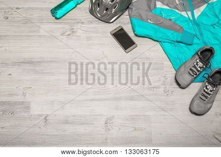 Fitness concept with mobile phone with earphones and sport footwear over wooden background. Top view.