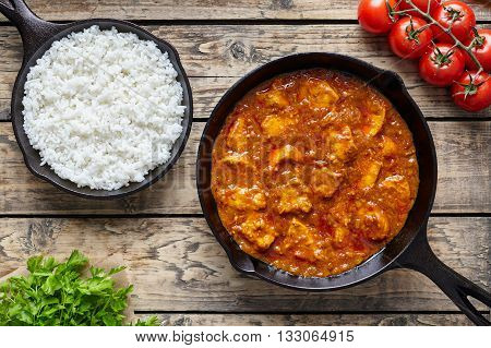Chicken tikka masala traditional Asian spicy meat food with rice tomatoes and parsley in cast iron pan on vintage wooden background