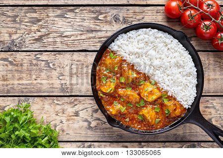 Chicken tikka masala Asian traditional spicy meat food and rice in cast iron skillet with tomatoes, butter and parsley on vintage wooden background