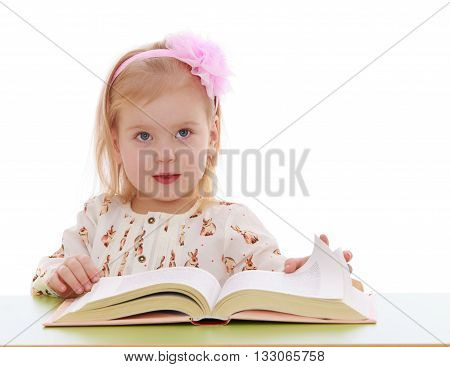 Cute little blonde girl with a pink bow on his head is reading a thick book . Girl sitting at the table. Close-up - Isolated on white background