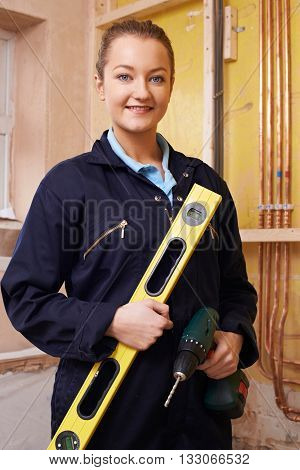 Portrait Of Female Builder With Spirit Level And Electric Drill