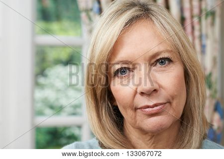 Head And Shoulders Portrait Of Unhappy Mature Woman At Home