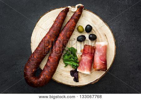 Spanish serrano ham, olives and sausage on a black slate
