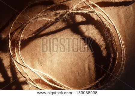 Skein of twine on old brown paper with shadow