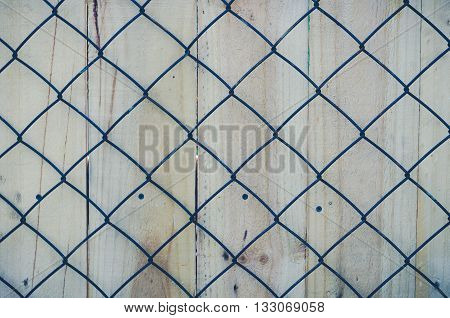 Metal mesh for fencing. Closeup on the background of wooden boards.