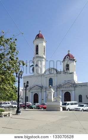 CIENFUEGOS - DECEMBER 2: Tourists walking in front of Cathedral on 2 December 2015 in Cienfuegos, Cuba. Cathedral is located in the Jose Marti Plaza.