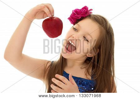 Beautiful girl holding on outstretched hand a big red Apple, the girl opened her mouth to this Apple to bite . Close-up - Isolated on white background
