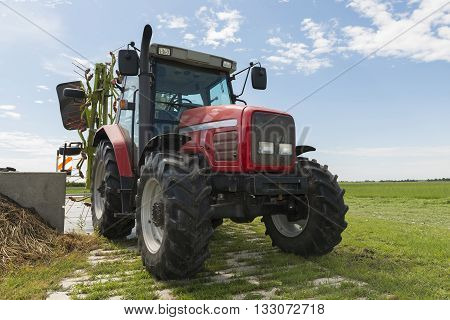 red tractor with tedder nearby a field