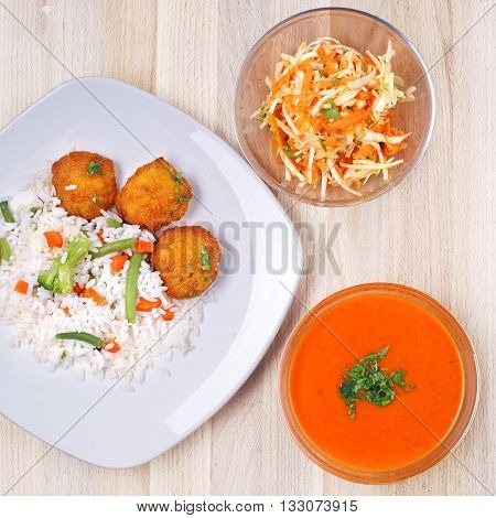 Tomato soup, coleslaw salad in glass bowls and plate with rice with checken nugets and vegetables on rustic wooden table. top view