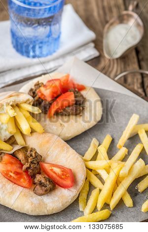 Gyros with potatoes meat tomato on pita bread parchment and dzatziki in a gravy boat napkin vertical