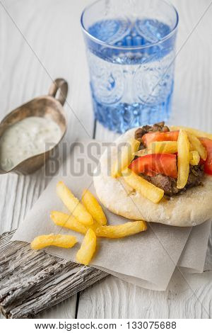 Gyros with fried potatoes meat tomato on pita bread stand and dzatziki in a gravy boat glass vertical