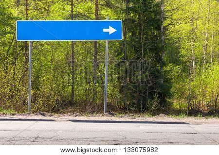 Blue road sign near highway with blank place for destination name and white direction arrow