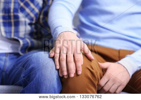 Two homosexuals holding each other hands closeup