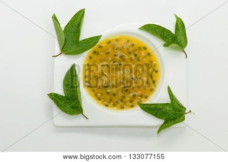 Passion fruit juice wht green leaves on white plate