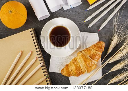 Top view of wooden desktop with orange croissant coffee cup stationery wheat spikes and paper rolls