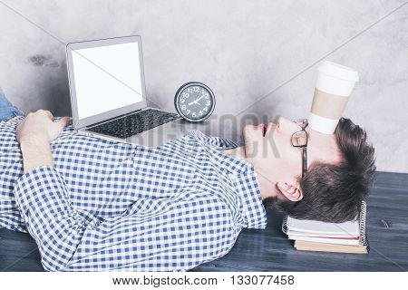 Young caucasian businessman with blank white laptop screen sleeping on wooden desktop with coffee cup on forehead. Mock up
