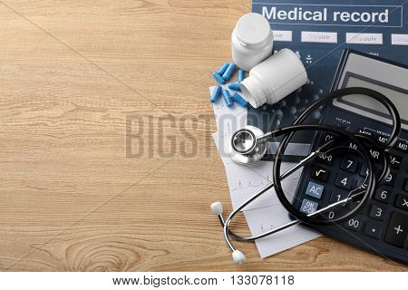 Medical concept. Medical record with  stethoscope and pills on wooden background