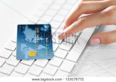 Woman hand and credit card on keyboard, closeup