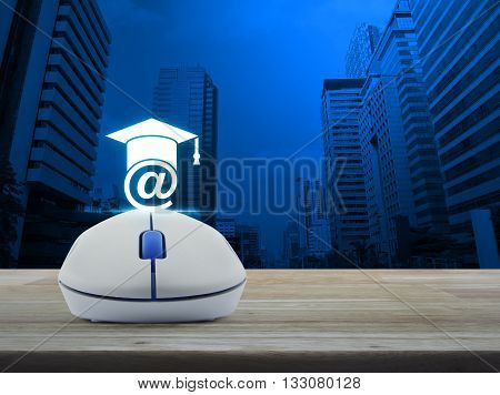 Wireless computer mouse with e-learning icon on wooden table in front city tower background Study online concept