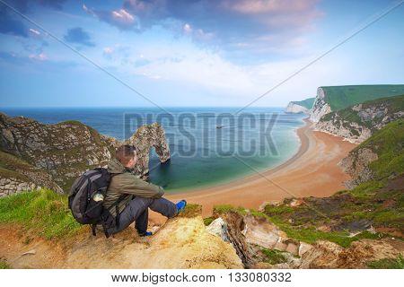 Man watching sunrise over Jurassic coast of Dorset, UK