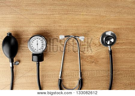 Medical manometer and a stethoscope on wooden background