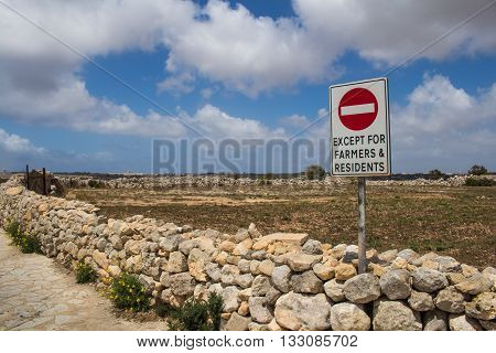 Fence made of stones lining a field. No entrance sign. Blue sky with intense white clouds. Mediterranean island Malta.