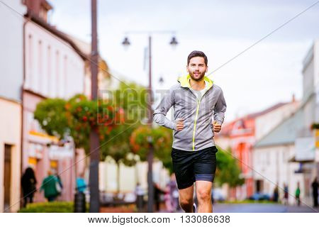 Young hipster man in gray sweatshirt running in town, main street